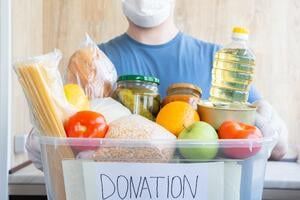 caucasian-man-in-white-medical-mask-holds-in-his-hands-donation-box-full-of-various-food